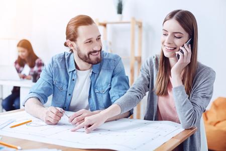 Mira aquí. Hombre barbudo sonriente apoyando los codos sobre la mesa y girando la cabeza mientras mira a su colega