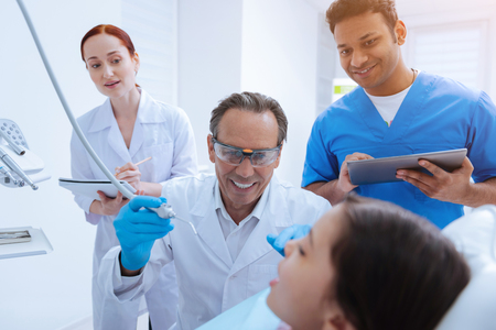 Look forward. Joyful dentist keeping smile on his face and wearing protective glasses while going to treat bad teeth Stock Photo