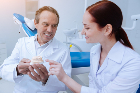 Medical workers. Handsome mature stomatologist expressing positivity while demonstrating artificial jaw to his assistant Stock Photo