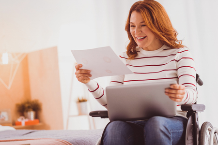 Great result. Attractive freelance worker keeping smile on her face while looking at document Stock Photo