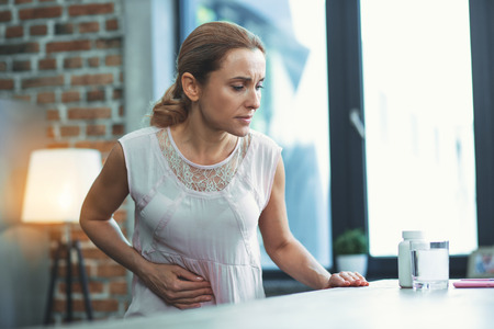 Stomach hurts. Pensive mature woman staying and putting hand on tummy