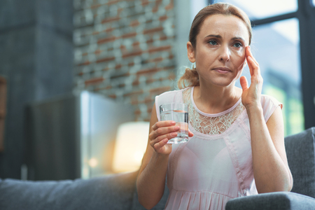 Migraine triggers. Low angle of pleasant mature woman posing on blurred background while carrying glass of water Stock Photo