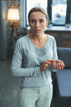Monitor health. Exhausted mature woman standing and monitoring heartbeat