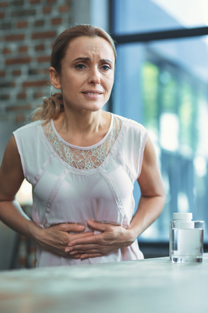 Problem with digestion. Diseased mature woman posing on blurred background and putting hands on tummy