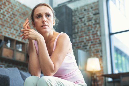 Pervasive mood disorder. Low angle of reflective mature woman posing on blurred background and looking aside Stock Photo