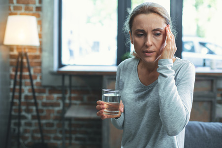 Shortness of breath. Unhappy mature woman sweating and touching head
