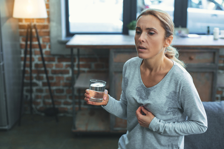 Période difficile. Femme mature triste transpiration et tenant un verre d'eau