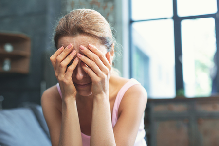 Emotional burden. Mournful mature woman covering face and weeping