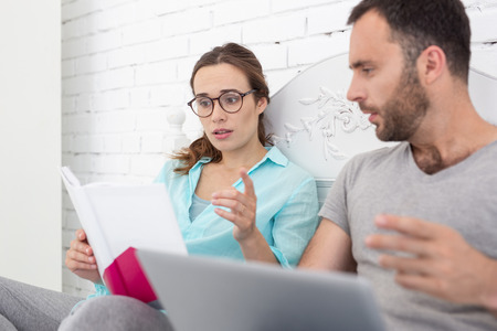 New information. Energetic pregnant woman and man looking at book and communicating Stock Photo