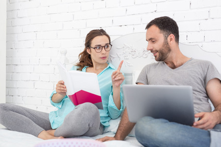 Valuable advice. Attractive pregnant woman and man studying book and communicating