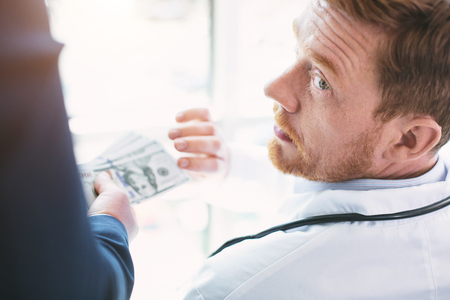 Money decided everything. Amoral unprincipled doctor wearing a uniform and a man giving him a bribe Stock Photo