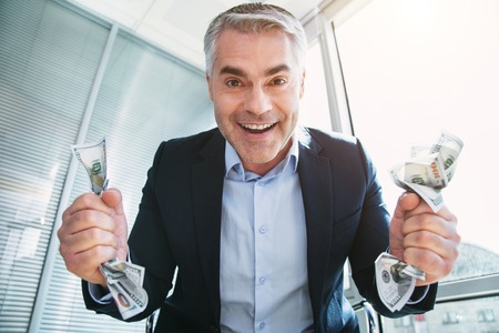Immoral grey-haired man smiling and holding a lot of money Stock Photo