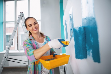 Exuberant dark-haired woman holding a roller and painting the walls Stock Photo