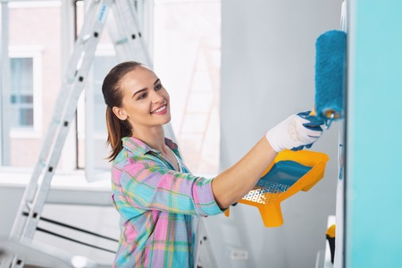 Interesting idea. Exuberant slim woman painting the wall in blue colour and wearing gloves