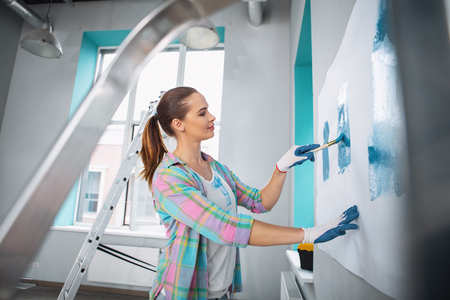 Pleased slim woman painting the wall in blue colour and wearing gloves