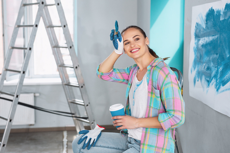 Nice cheerful woman having a coffee break while redecorating her room Banque d'images
