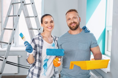 Exuberant professional painters smiling and holding a roller and brush