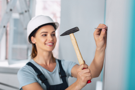 Joyful experienced builder smiling and hammering a nail into the wall Stock Photo