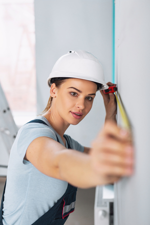 Determined professional builder wearing a uniform and holding a measuring tape