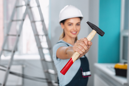 Inspired female builder holding a hammer and smiling