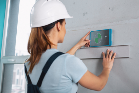 Female professional builder wearing a uniform and working with her instruments