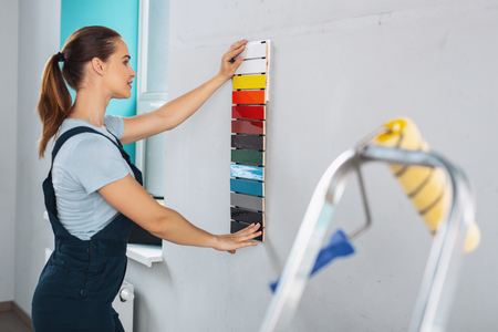 Cheerful professional designer wearing a uniform and choosing a paint for walls