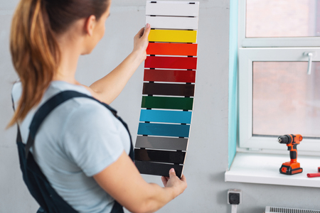 Female professional designer wearing a uniform and choosing a paint for walls Banque d'images