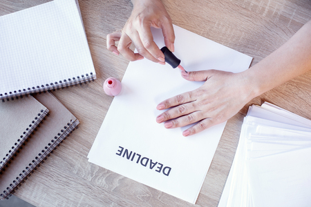 No matter what. Close up of smooth female hands lying on paper with deadline and using nail polish Banco de Imagens