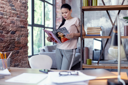 Interesting article. Appealing female employee standing while studying magazine