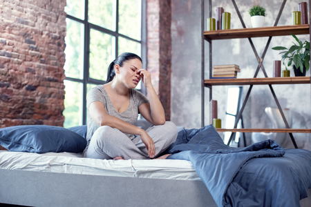 Headache symptoms. Painful stressed woman resting on bed and touching nose bridge Stock Photo