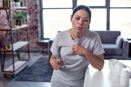 Maladie respiratoire. Bouleversé malheureuse femme transpirant et tenant de l'eau