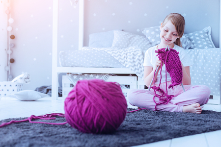 Knitting a gift for mommy. Adorable young lady smiling while sitting on a carpet and working on a new knitted masterpiece in her bedroom. Stockfoto