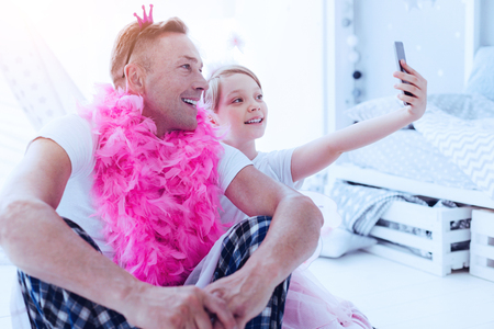Say cheese. Funny mature man wearing a feather boa and a little crown smiling while sitting next to his preteen daughter and taking a self portrait with her.