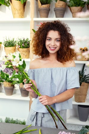 Flower decorator. Delighted nice woman holding flowers while working in the flower shop
