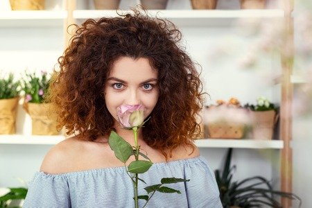 Magnetic look. Delighted happy woman looking at you while smelling a rose