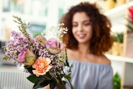 Floristic masterpiece. Selective focus of a flower bouquet being in hands of a cheerful attractive woman Фото со стока