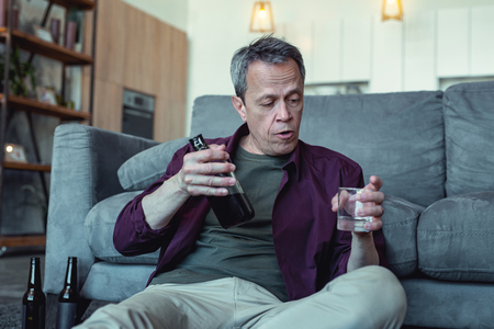 Glass of vodka. Mature badly looking man with facial wrinkles sitting with glass of vodka being alcohol addicted Фото со стока