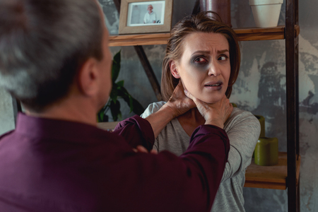 Furious man. Furious irritated man wearing purple shirt feeling overemotional while strangling young woman