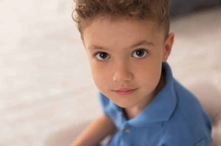 Handsome boy. Handsome dark-eyed little boy with nice dark curly hair feeling very satisfied while playing at home Stok Fotoğraf