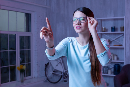 Modern technology. Focused female freelancer touching glasses and pointing with finger Stock Photo