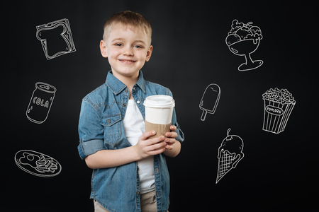 Tasty hot drink. Cute kind boy smiling and feeling glad while standing with a cup of tasty hot coffee for his mother