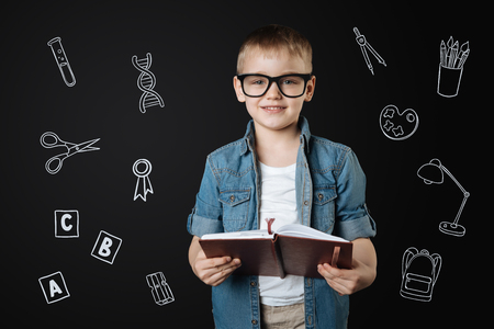 Future teacher. Cheerful smart little boy wearing glasses and holding a notebook while having fun and pretending to be a teacher Banco de Imagens
