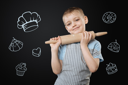 Adorable cook. Pretty little boy enjoying cooking and smiling while standing with a wooden rolling pin in his hands