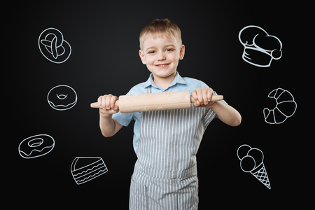 Boy cooking. Positive enthusiastic little boy smiling happily and wearing an apron while holding a big wooden rolling pin