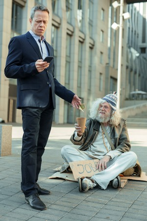 Rich and poor. Elderly rich successful businessman feeling helpful while giving some money to poor man
