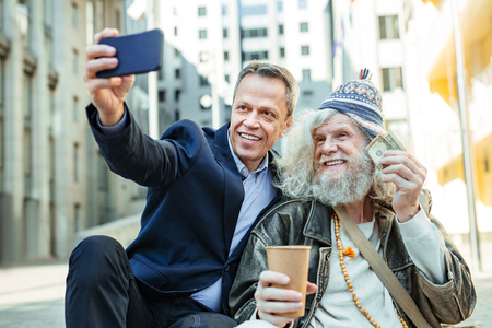 Elderly hippy. Funny elderly hippy man smiling broadly while taking picture with supportive helpful businessman Stock Photo