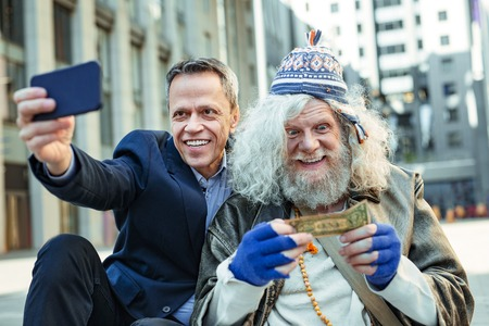 Surprised vagrant. Elderly homeless vagrant feeling extremely surprised after receiving money from kind-hearted office worker Reklamní fotografie