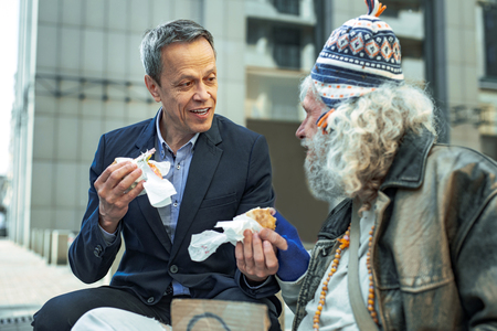 Take care. Prosperous white collar worker feeling good while taking care of street person giving him piece of burger