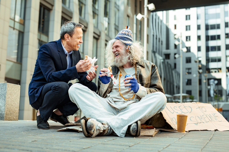 Joyful communication. Hippy starving man wearing tattered clothes enjoying communication with kind-hearted businessman