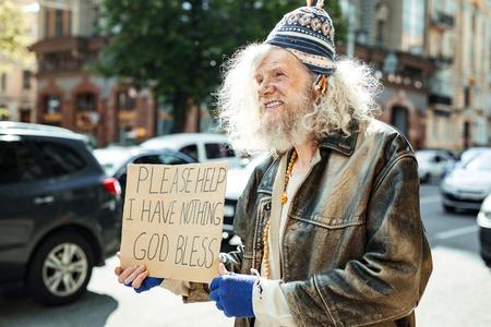 Traffic jam. Elderly hippy man feeling hopeless while begging for at least some help standing near traffic jam